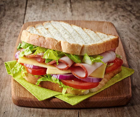 cutting vegetables: Sandwich with ham, cheese and fresh vegetables on wooden cutting board