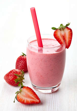 Glass of strawberry smoothie and fresh strawberries