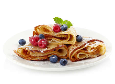 Plate of pancakes with fresh raspberries and blueberries isolated on white background