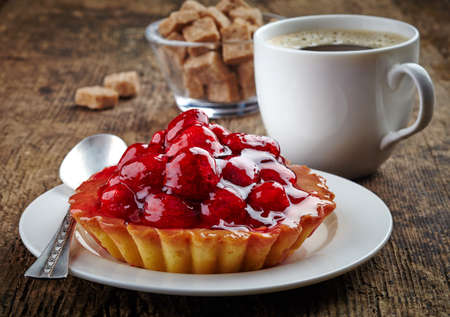 coffee jelly: Plate of raspberry tart and cup of coffee on wooden background