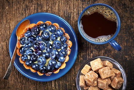 coffee jelly: Plate of blueberry tart and cup of coffee on wooden background Stock Photo
