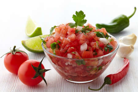 Bowl of fresh salsa dip and ingredients on white wooden background Stock Photo