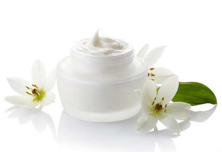 productos naturales: Tarro blanco de crema cosmética y flores aisladas sobre fondo blanco
