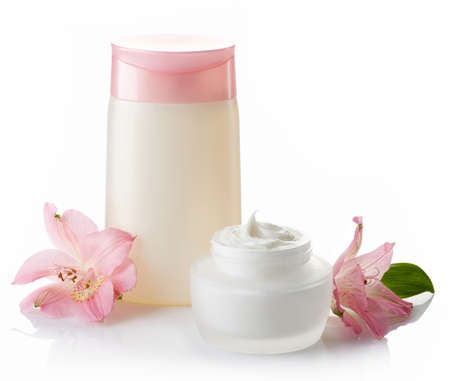 Bottle of cosmetic lotion and jar of cream isolated on white background