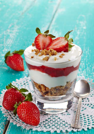 Healthy layered dessert with cream, muesli and fresh strawberry sauce on blue wooden background