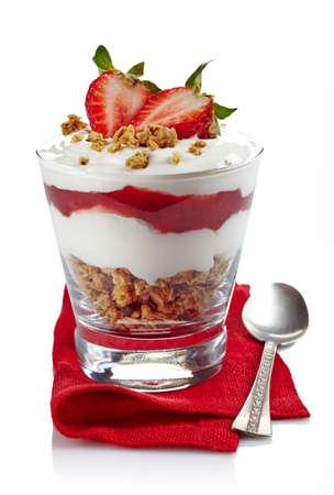 mermelada: Postre en capas saludable con crema, muesli y salsa de fresa fresca en mantel rojo aislado en fondo blanco