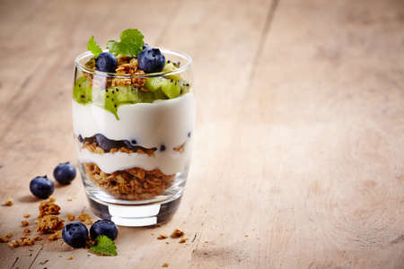 Healthy layered dessert with cream, muesli, kiwi and blueberries on wooden background with space for text Reklamní fotografie - 28111612