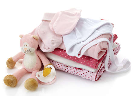 Stapel van roze babykleertjes, fopspeen en speelgoed op een witte achtergrond Stockfoto