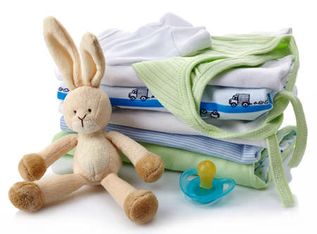 Pile of green and blue baby clothes, pacifier and toy isolated on white background