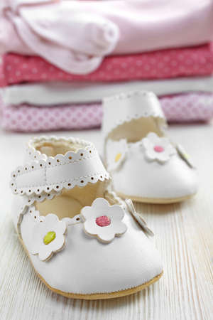White baby shoes and pile of pink clothes on white wooden background photo
