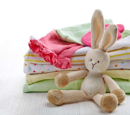 Pile de vêtements de bébé colorés et jouet en bois sur fond blanc