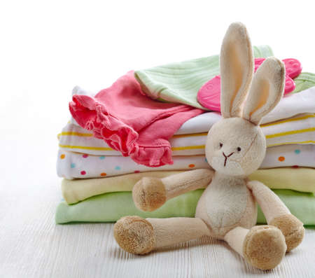 pile of clothes: Pile of colorful baby clothes and toy on white wooden background Stock Photo