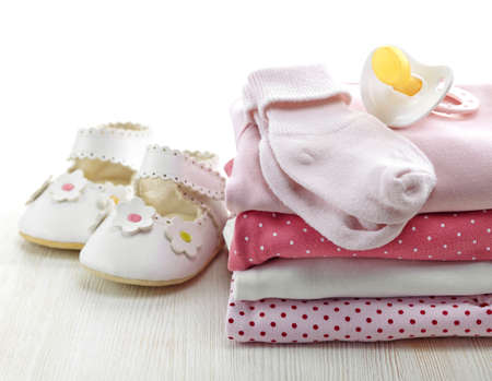 Pile of pink baby clothes and pacifier on white wooden background