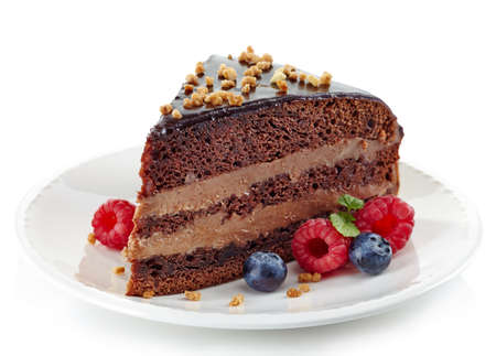Morceau de gâteau au chocolat et petits fruits frais isolés sur fond blanc