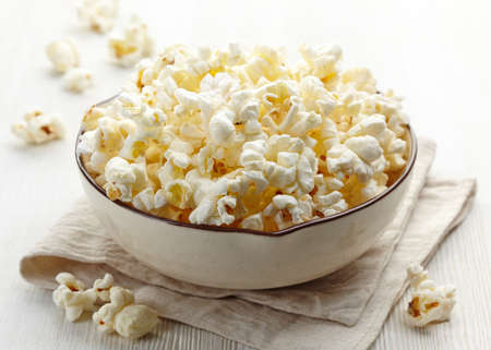 bowls of popcorn: Bowl of fresh popcorn on white wooden