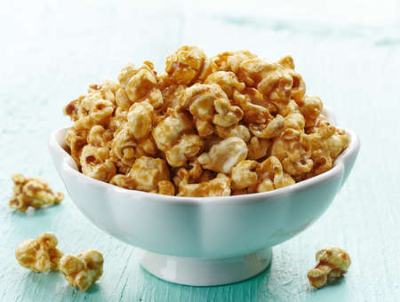 bowl of popcorn: Bowl of sweet caramel popcorn on blue wooden background Stock Photo