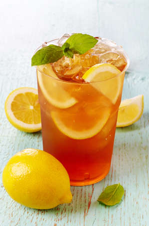 ice lemon tea: Plastic glass of ice tea with lemon and mint on blue wooden background