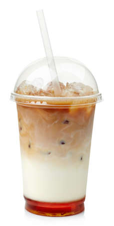 Iced coffee with caramel syrup in plastic glass isolated on white background