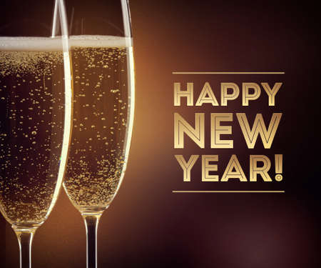 SPARKLING WINE: Two glasses of champagne with happy New year text on black background Stock Photo