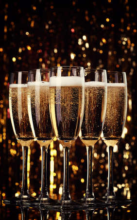 Five flutes of champagne on bokeh background