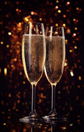 Two flutes of champagne on bokeh background