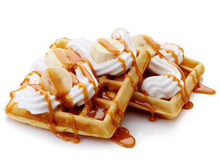 waffle: Belgian waffles with whipped cream, caramel sauce and bananas isolated on white background