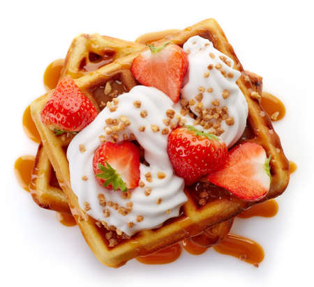 Belgian waffles with caramel sauce, whipped cream and strawberries isolated on white background (top view)