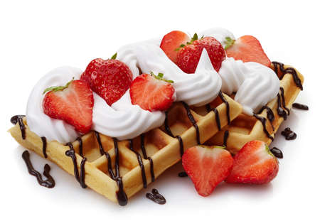 Belgian waffles with whipped cream, strawberries and chocolate sauce isolated on white background