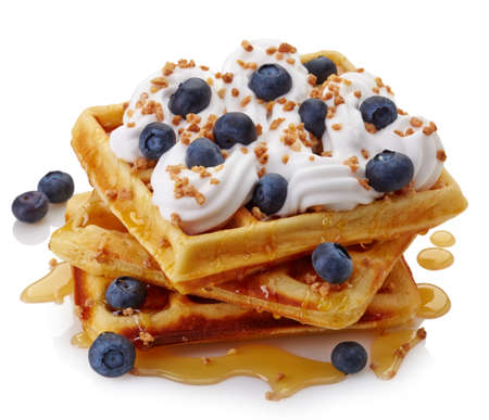 Belgian waffles with whipped cream, blueberries and maple syrup isolated on white background