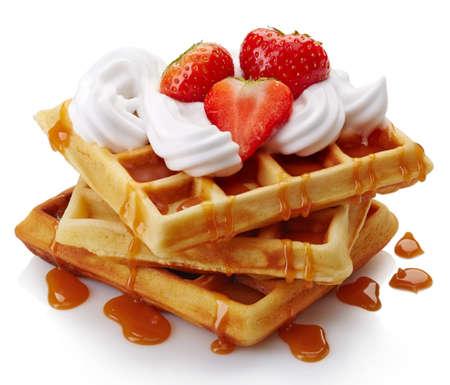 waffles: Gofres belgas con crema batida, fresas y salsa de caramelo aislados en el fondo blanco Foto de archivo