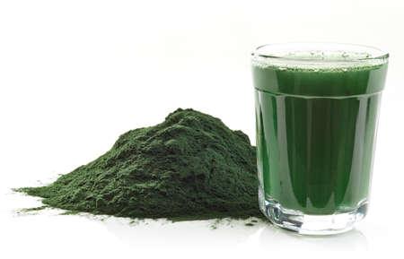 zumo verde: Pila de polvo de algas espirulina y bebida spirulina aislado en fondo blanco