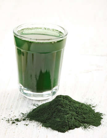Stack of spirulina algae powder and spirulina drink white wooden background Imagens