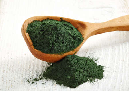 algaes: Wooden spoon of spirulina algae powder on white wooden background