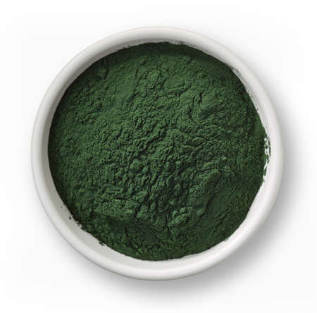 White bowl of spirulina algae powder isolated on white background Imagens