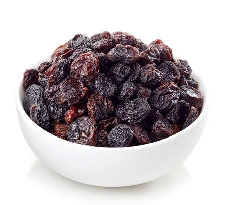 grapes: Cuenco de pasas oscuros aislado sobre fondo blanco