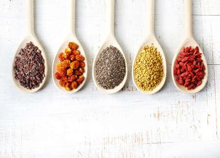 chia: Wooden spoons of various superfoods on white wooden background