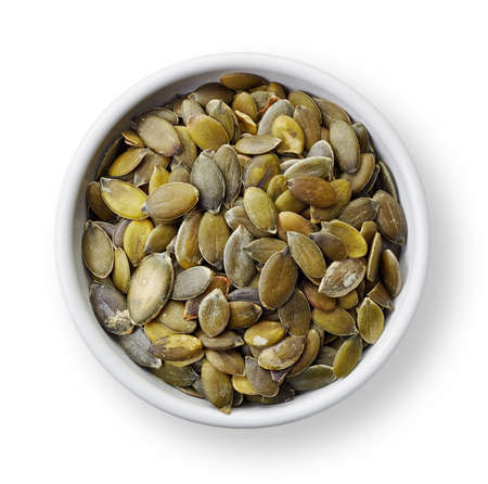 pumpkin seeds: White bowl of pumpkin seeds isolated on white background