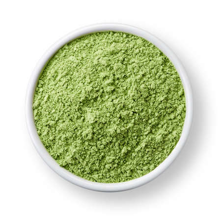 green powder: White bowl of healthy wheat sprouts powder isolated on white background Stock Photo