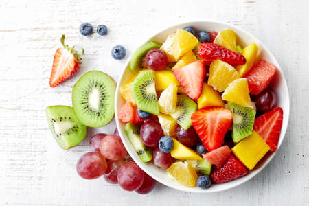 citruses: Bowl of healthy fresh fruit salad on wooden background. Top view.