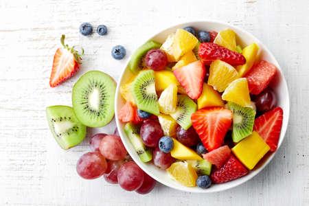 owoców: Puchar zdrowe sałatki ze świeżych owoców na tle drewnianych. Widok z góry.