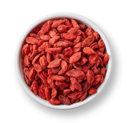 White bowl of goji berries isolated on white background
