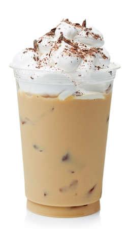 Café glacé couvert de crème fouettée dans le verre en plastique isolé sur fond blanc
