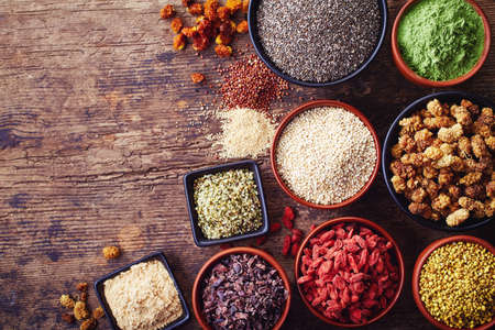 Bowls of various superfoods on wooden  background