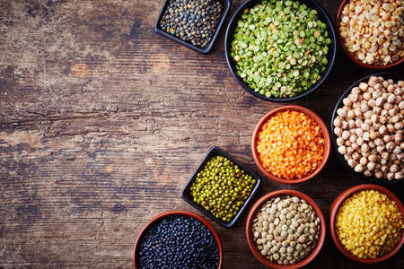 Bowls of various legumes (chickpeas, green peas, red lentils, canadian lentils, indian lentils, black lentils, green lentils; yellow peas, green mung beans) on wooden background Stockfoto