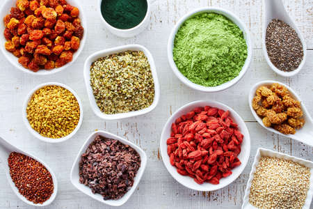 alimentacion sana: Cuencos blancos de diversos superalimentos en el fondo de madera blanca