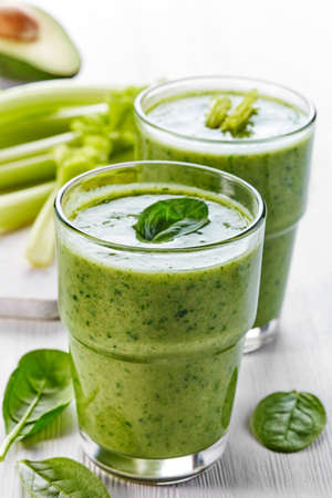 Two glasses of healthy green vegetable and fruit smoothie Imagens