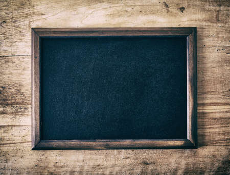 Vintage slate blank blackboard on wooden background