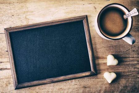 キャンディの心と木製の背景にコーヒーのカップを持つ空の黒板