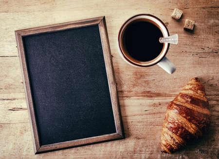 pizarron: Pizarra en blanco con croissant y una taza de café sobre fondo de madera