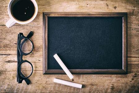 チョーク、ガラス、木製の背景にコーヒーの部分で空の黒板